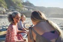 Donne sorridenti amiche che parlano sulla spiaggia soleggiata durante il ritiro yoga — Foto stock