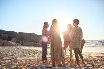Женщины, стоящие в кругу на солнечном пляже во время йоги отступления — стоковое фото