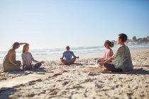 Группа медитирует на солнечном пляже во время йоги — стоковое фото
