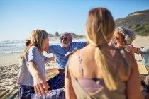 Amici che si abbracciano in cerchio sulla spiaggia soleggiata durante il ritiro yoga — Foto stock