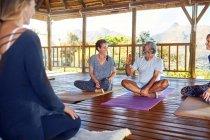Мужчина и женщина разговаривают во время занятий йогой в хижине на йоге — стоковое фото