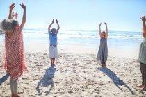 Groupe debout avec les bras levés en cercle sur la plage ensoleillée pendant la retraite de yoga — Photo de stock