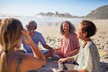 Amis assis en cercle sur la plage ensoleillée pendant la retraite de yoga — Photo de stock
