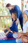 Жіночий інструктор налаштування студентів плечі під час йоги відступ — стокове фото