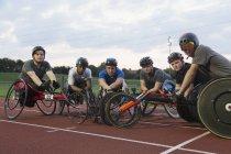 Retrato confiante, determinado treinamento de atletas paraplégicos para corrida em cadeira de rodas em pista de esportes — Fotografia de Stock