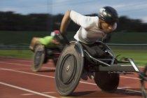 Determinato giovane atleta paraplegico maschile che corre lungo la pista sportiva in gara su sedia a rotelle — Foto stock