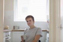 Ritratto fiduciosa giovane donna in sedia a rotelle bere caffè in cucina appartamento — Foto stock