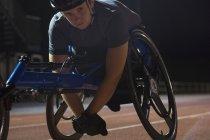 Retrato determinado joven mujer parapléjico atleta entrenamiento para la carrera en silla de ruedas en pista deportiva por la noche - foto de stock