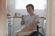 Retrato sonriente, joven confiada en silla de ruedas bebiendo té en la cocina del apartamento - foto de stock