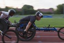 Визначено параплідіческой спортсменів прискорення вздовж спортивного треку в інвалідному візку гонки — стокове фото