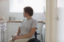Thoughtful young woman in wheelchair drinking tea in apartment kitchen — Stock Photo