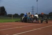 Paraplegic athletes huddling on sports track, training for wheelchair race at night — Stock Photo