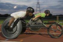 Paraplegic спортсменів прискорення уздовж спортивного треку в інвалідному візку гонки — стокове фото