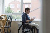 Jeune femme en fauteuil roulant avec écouteurs à la fenêtre — Photo de stock