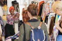Молода жінка з камерою телефону фотографування друзів покупки в магазині одягу — стокове фото