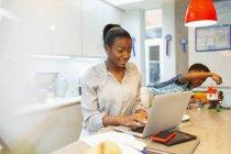 Niño jugando al lado de la madre trabajando en el ordenador portátil en la cocina - foto de stock