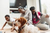 Multi-generation family playing with dog in living room — Stock Photo