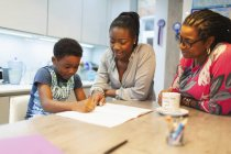 Multi-generation family coloring in kitchen — Stock Photo