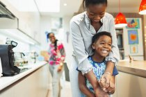 Affectionate mother and son hugging in kitchen — Stock Photo