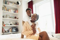 Portrait affectionate mother and son hugging on bed — Stock Photo
