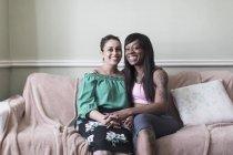 Портрет щасливе, ласкаве лесбійське подружжя тримає руки на дивані вітальня — стокове фото