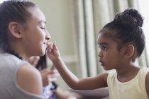 Linda niña aplicando brillo de labios a los labios de la hermana - foto de stock
