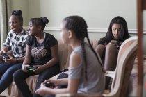 Entre amies jouant au jeu vidéo sur le canapé du salon — Photo de stock