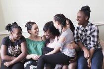 Pares da lésbica com as crianças no sofá da sala de visitas — Fotografia de Stock