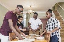 Frères et sœurs adolescents mettant la table — Photo de stock