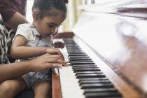 Цікавий малюк дівчина грає на фортепіано — стокове фото