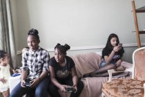 Tween girl friends playing video game on living room sofa — Stock Photo