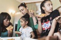 Лесбийская пара и дочери едят пиццу — стоковое фото