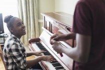 Усміхнені підлітка дівчата грають на фортепіано — стокове фото