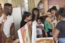 Famille appréciant la pizza à la maison — Photo de stock