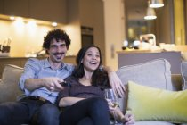 Happy couple watching TV and drinking white wine on living room sofa — Stock Photo