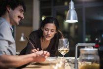 Casal jantar com pauzinhos e beber vinho branco na cozinha do apartamento — Fotografia de Stock