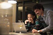 Casal feliz usando laptop e beber vinho branco no apartamento à noite — Fotografia de Stock