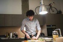 Мужчина режет овощи, готовит ужин на кухне — стоковое фото