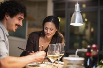 Couple eating with chopsticks and drinking white wine in apartment kitchen — Stock Photo