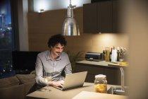 Homme buvant du vin blanc à l'ordinateur portable dans la cuisine de l'appartement la nuit — Photo de stock