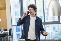 Man talking on smart phone in apartment — Stock Photo