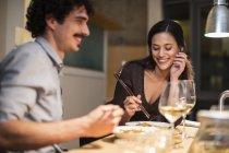 Feliz casal jantando com pauzinhos e bebendo vinho branco — Fotografia de Stock