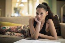 Ritratto donna sicura in pigiama che legge scartoffie sul divano del salotto — Foto stock