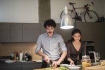 Vegetales de corte par, cocinar la cena en la cocina - foto de stock