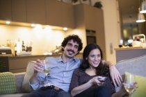 Happy couple drinking white wine and watching TV on apartment sofa — Stock Photo