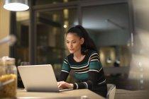 Mujer enfocada usando portátil en casa por la noche - foto de stock