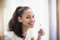Портрет улыбающейся, уверенной женщины, чистящей зубы в зеркале ванной — стоковое фото