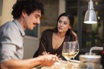 Casal jantando com pauzinhos e bebendo vinho branco em casa — Fotografia de Stock