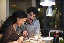 Couple dîner avec baguettes dans la cuisine de l'appartement — Photo de stock