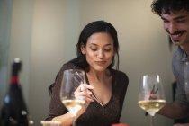 Coppia sorridente che cena con bacchette e beve vino bianco — Foto stock